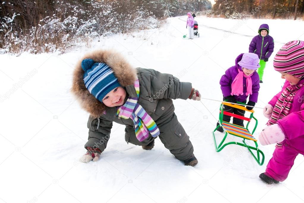 children with sleds in winter