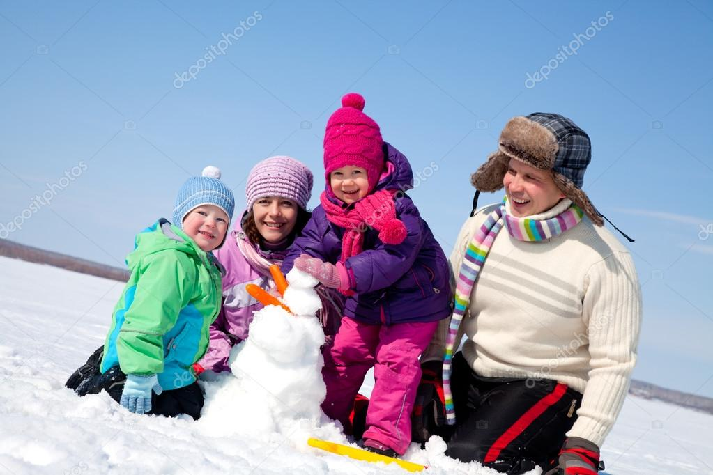 Happy family making snowman