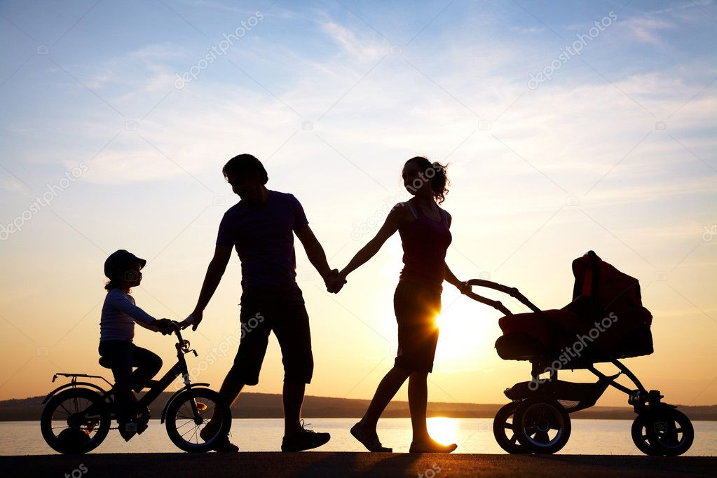 happy family walking on sunset