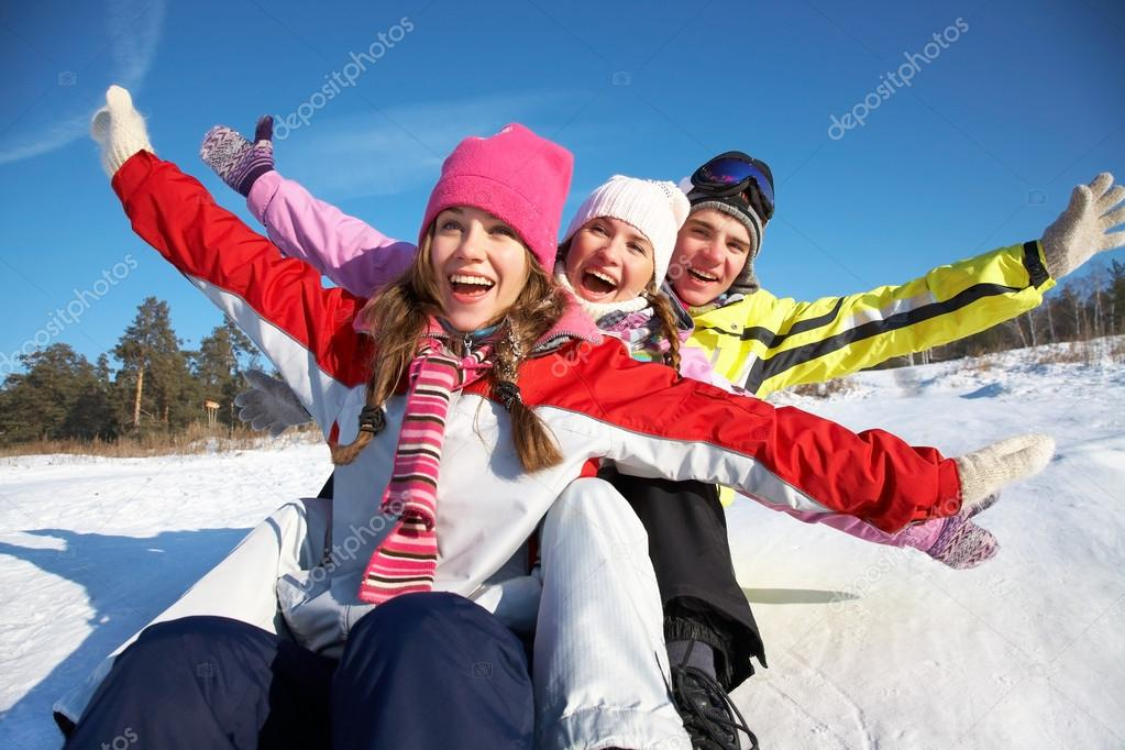 Group of teenagers slide downhill in wintertime stock vector