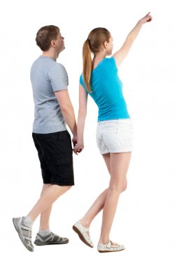 Back view of walking young couple