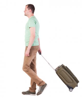 back view of walking man with suitcase. brunette guy in motio