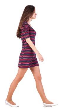 Side view of walking woman in dress .