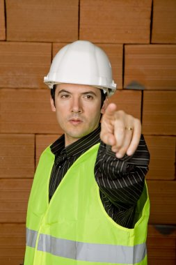 Engineer with yellow hat with a brick wall
