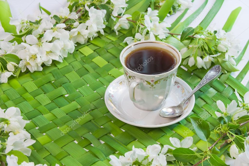 Cup of coffee with the sprigs of flowering apple-tree