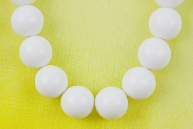 woman white beads on a yellow background