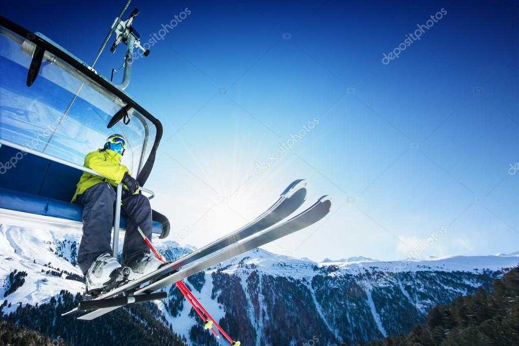 Skier siting on ski-lift - lift at sunny day and mountain