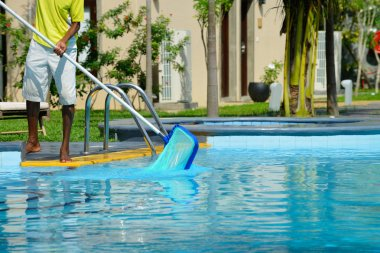 A man cleans the pool