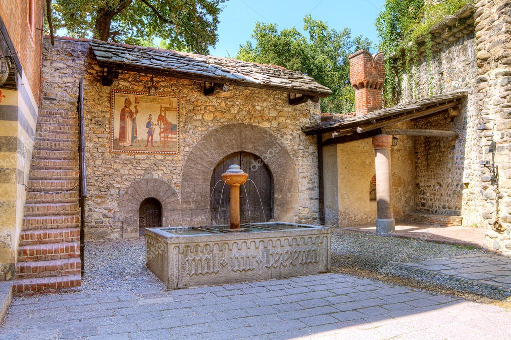 patio empedrado de castillo medieval de valentino aka castello del valentino pequea casa de piedra con puerta de madera antigua y fuente en turn