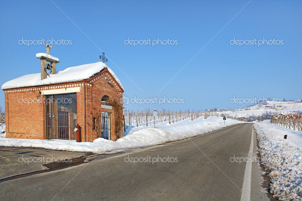 Roadside chapel and snowy vineyards. Piedmont, Italy.