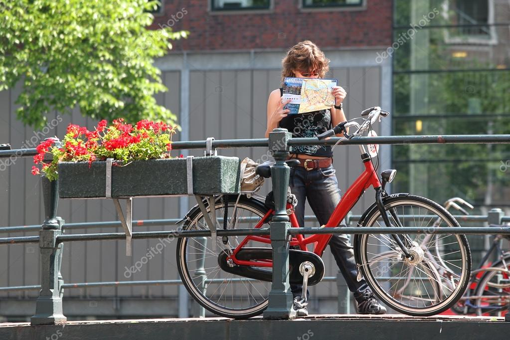 Tourist with map and bicycle Amsterdam Netherlands Stock