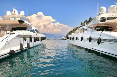 Two white luxury yachts on Mediterranean sea.