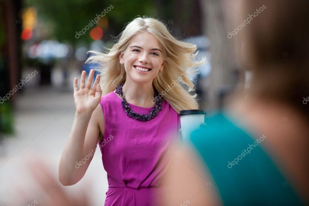 Woman Waving Hello on Street