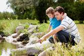 Fotografie Schlägerei und Sohn spielen am See