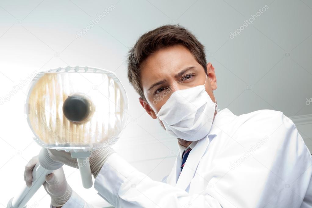 Dentist Holding Dental Lamp