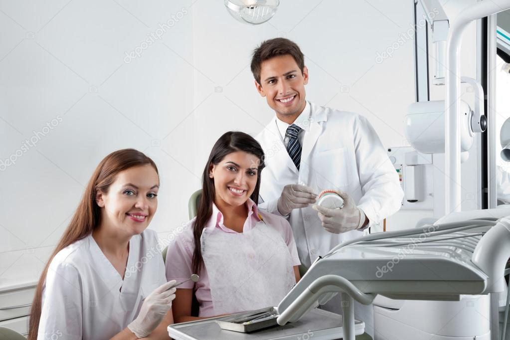 Dentist And Nurse With Patient In Clinic