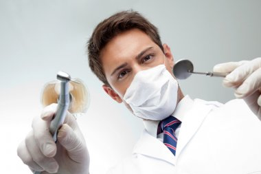 Dentist Holding Angled Mirror And Drill