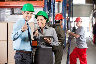 Supervisors Gesturing Thumbs Up At Warehouse