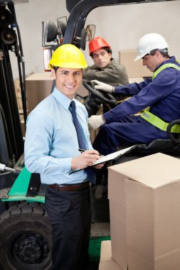 Portrait of supervisor writing on clipboard with foremen working at warehouse stock vector