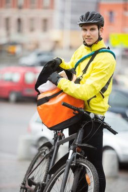 Male Cyclist Putting Package In Courier Bag On Street