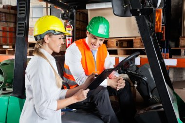 Supervisor Showing Clipboard To Colleague Sitting In Forklift