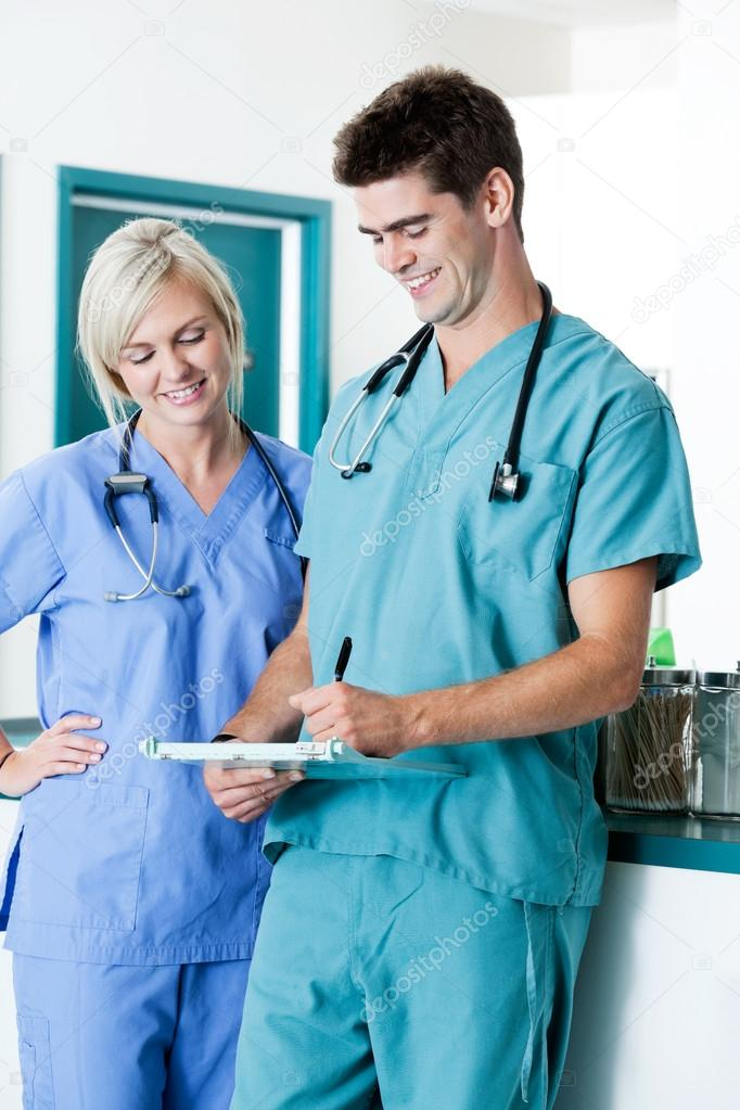 Male Doctor Writing On Clipboard With Colleague At Clinic