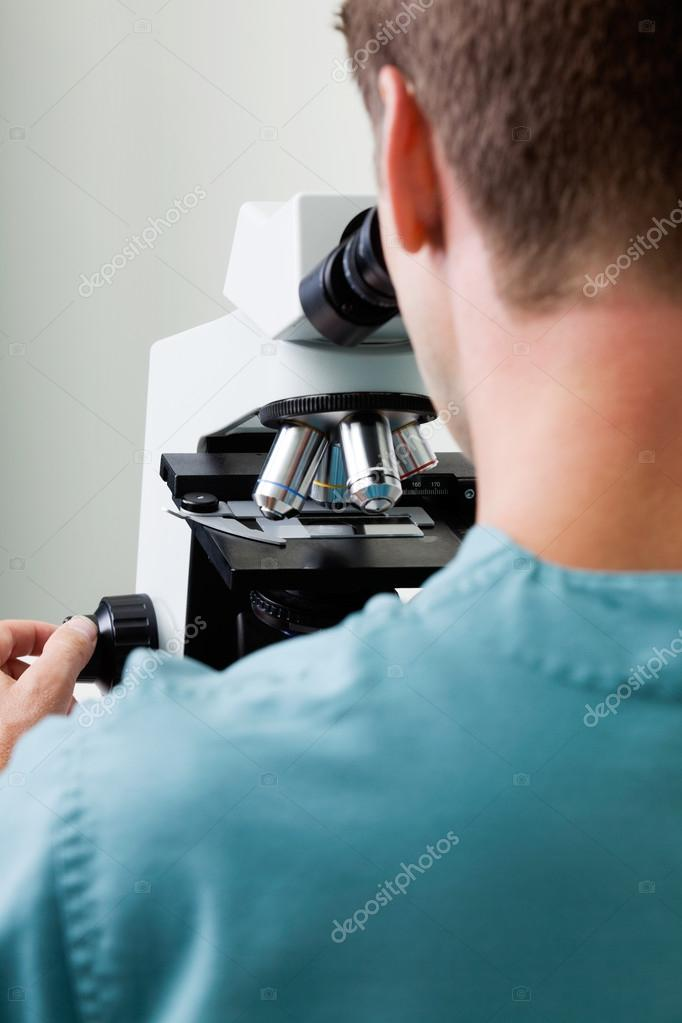Male Researcher Using Microscope In Laboratory