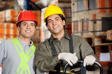 Portrait of two happy foremen wearing hardhats at warehouse stock vector