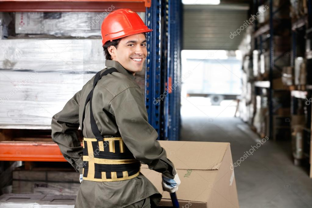 Warehouse Worker Pushing Handtruck With Cardboard Boxes