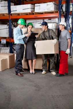 Foremen and supervisors discussing work at warehouse stock vector