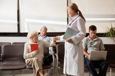 Doctor Holding Senior Woman's Hand