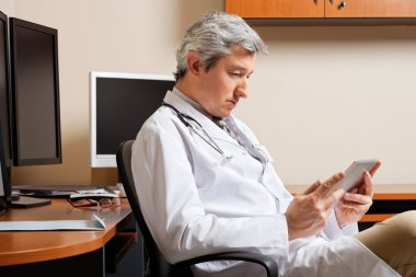 Serious Doctor Looking At Digital Tablet