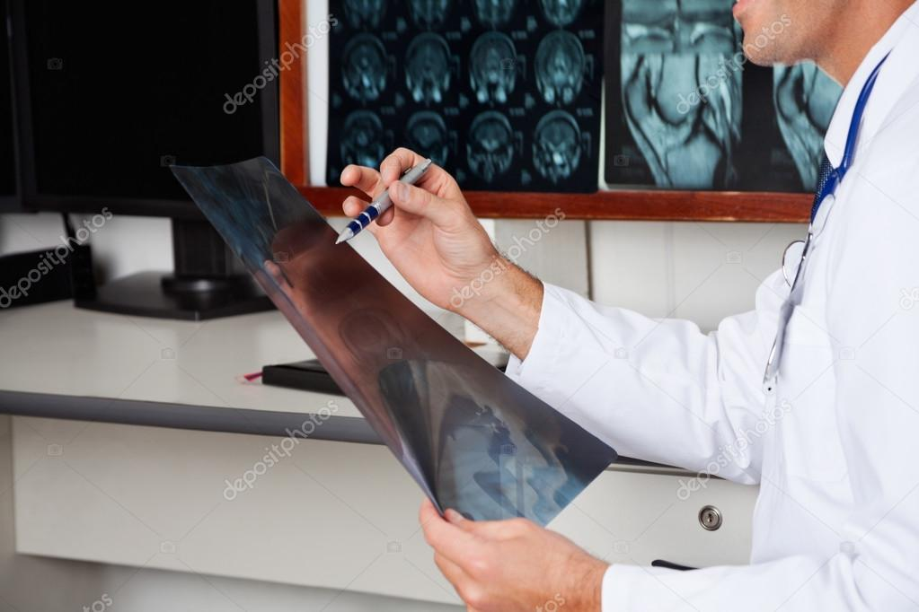 Midsection of male radiologist studying patient's x-ray