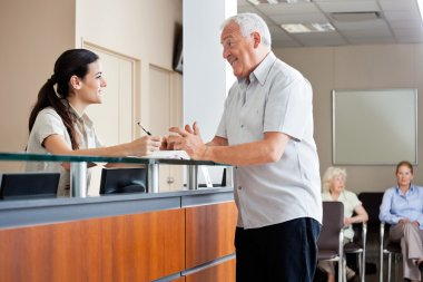 Senior man communicating with female receptionist while women sitting in background stock vector