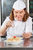 Fotografie Female Chef Adding Spices To Dish