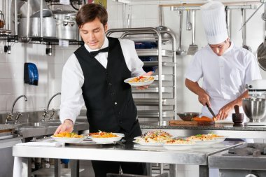 Waiter And Chef Working In Commercial Kitchen