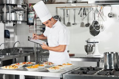 Chef With Clipboard Going Through Cooking Checklist