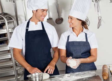 Happy Chefs Kneading Dough In Kitchen