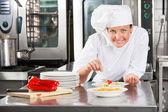 Šéfkuchař špetkou koření na potraviny