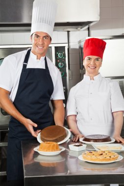 Happy Chefs With Variety Of Sweet Dishes