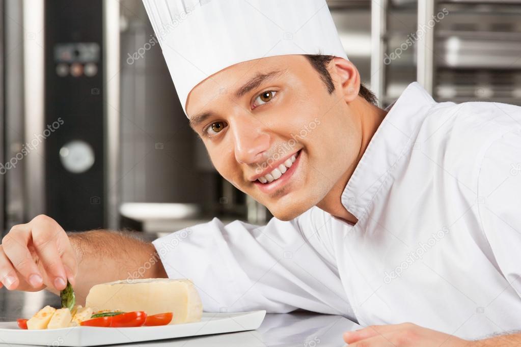 Happy Male Chef Garnishing Dish