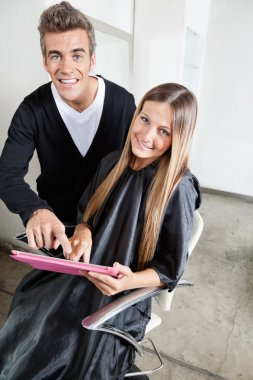 Hairstylist With Client Using Digital Tablet