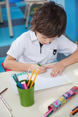 Little Boy Drawing At Desk In Art Class