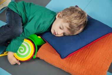 Cute boy sleeping with toy in kindergarten stock vector