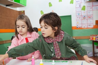 Little boy with girl painting at classroom desk in kindergarten stock vector