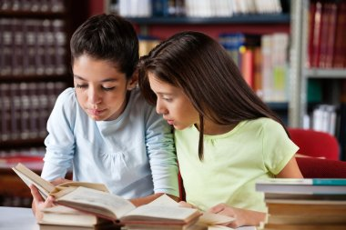 Schoolgirls Reading Book Together In Library