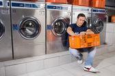 Fotografia uomo con cesto di vestiti seduto alla lavanderia a gettoni