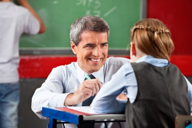 Teacher Looking At Schoolgirl Sitting At Desk