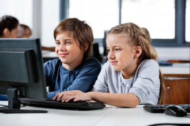 Boy And Girl Using Desktop Pc In School Computer Lab