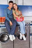 Fotografia felice coppia giovane seduto su lavatrici